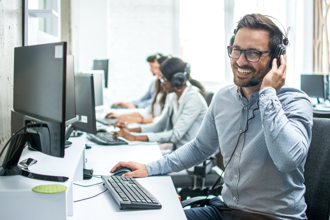 Man sitting at his desk smiling with a headset on his computer